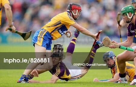 Wexford's Liam Og McGovern loses his helmet in a collision with Jack Browne of Clare