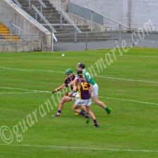 Cillian Kiley Offaly tries his best to keep put two Wexford players